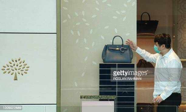 Man wears a face mask as he reaches for a bag in a Mulberry store in a shopping mall in Singapore on April 3 as the government imposed tighter...