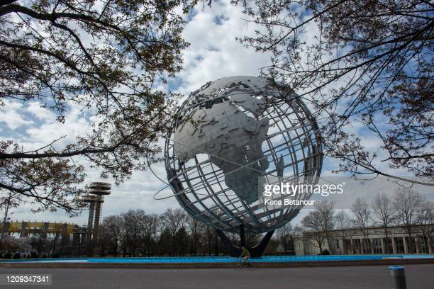 Man wears a face mask as he rides a bike next to Unisphere inside the Flushing Meadows Corona Park on April 7, 2020 in the Queens borough of New York...