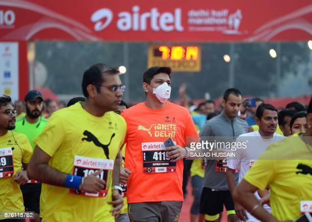 A man wears a face mask as he takes part in the Airtel Delhi Half Marathon 2017 in New Delhi on November 19 2017 / AFP PHOTO / SAJJAD HUSSAIN