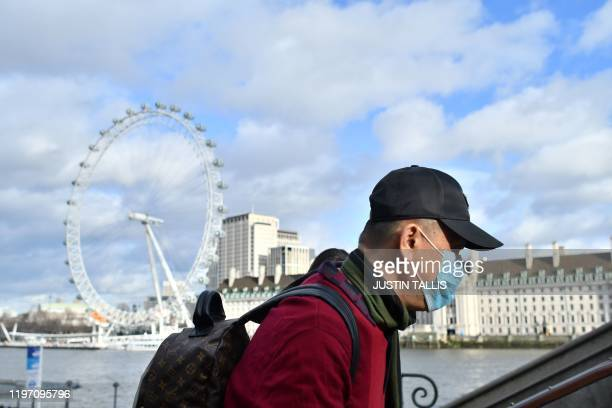 A man wears a face mask as he walks along the Thames embankment in central London on January 28 2020 Around 1500 people who came to Britain from the...