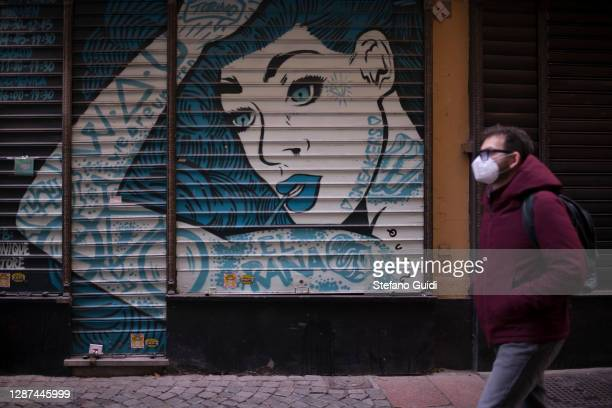 A man wears a face mask as he walks past a closed shop in Via Barbaroux on November 24 2020 in Turin Italy Via Barbaroux is an old area in Turin...