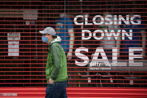 Man wears a face mask as he walks past a shop that is closing down on October 18, 2020 in Cardiff, Wales. Many UK businesses are announcing job...