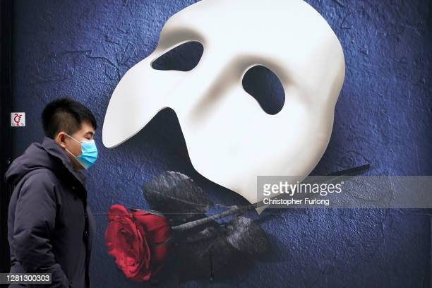 Man wears a face mask as he walks pasta a Phantom of the Opera advertisement on October 20, 2020 in Manchester, England. Talks between the Housing...