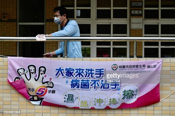 A man wears a face mask while cleaning a handrail behind a sign telling students how to wash their hands to prevent the COVID19 corona virus at a...