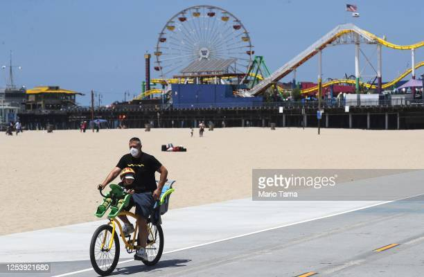 A man wears a face mask while cycling on Santa Monica beach amid the COVID19 pandemic on July 02 2020 in Santa Monica California Beginning July 3 Los...