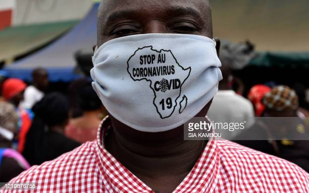 """Man wears a face mask with a message on that reads """"stop coronavirus"""" written inside a map of Africa, on April 24, 2020 in a street of Abobo, a..."""