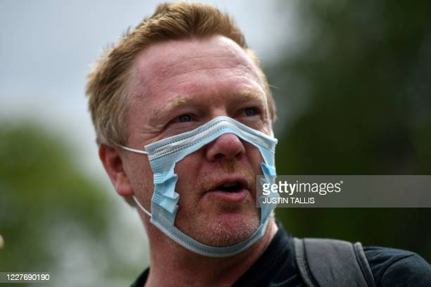 "Man wears a face mask with the centre removed as people gather to listen to speakers at a protest organised by ""Keep Britain Free"" in London on July..."