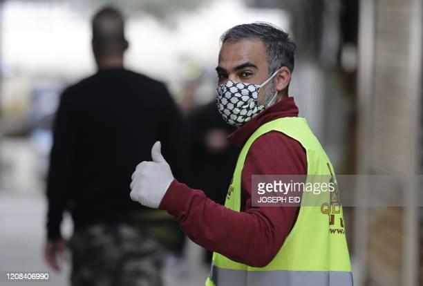 Man wears a face mask with the patterns of the Kaffiyeh, the chequered scarf that is worn by Palestinians to symbolise struggle, made Palestinian...