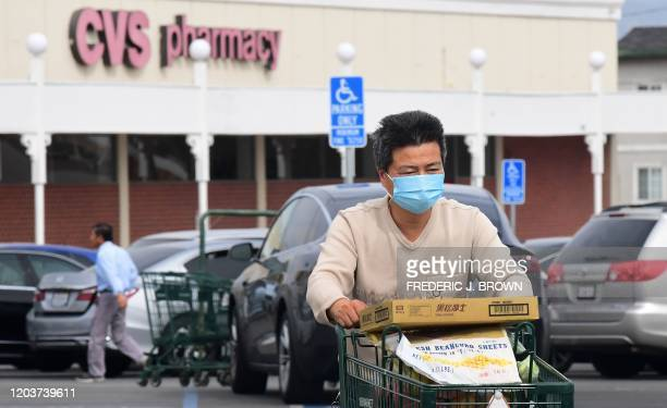 A man wears a facemask while pushing his shopping cart in Alhambra California on February 27 2020 Health and emergencymanagement officials said today...
