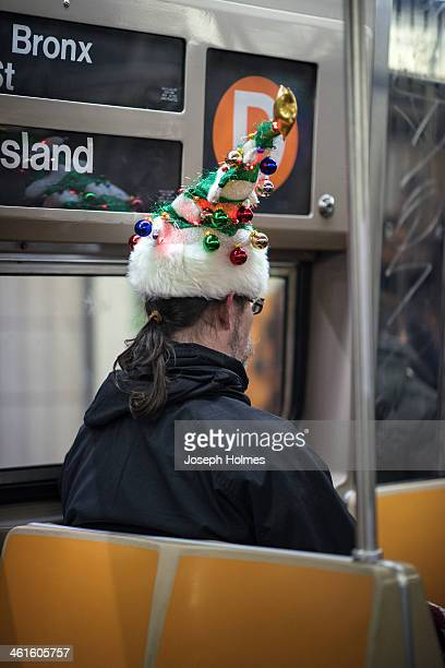 Man wears a festive Christmas tree hat, with ornaments, a star tree-topper, and working lights, as he rides the D train under Manhattan.