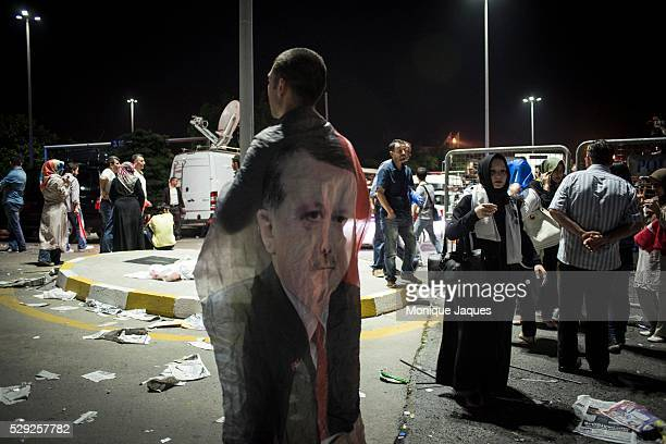 A man wears a flag showing the face of Erdogan AKP Supporters at Ataturk International Airport come out by the thousands to support Prime Minister...