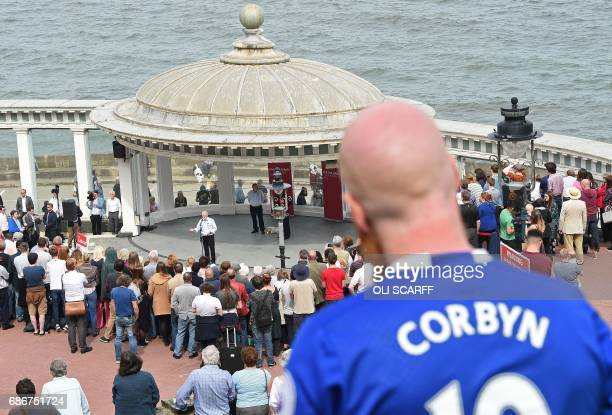 A man wears a football shirt with the words 'Corbyn' as he llistens to Britain's main opposition Labour Party leader Jeremy Corbyn address supporters...