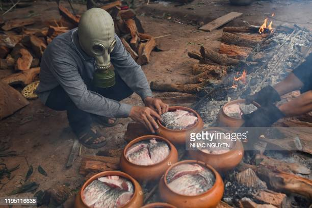 Man wears a gas mask while cooking fish in claypots over wood fire in Ha Nam province on January 21, 2020 ahead of the Lunar New Year. - The braised...