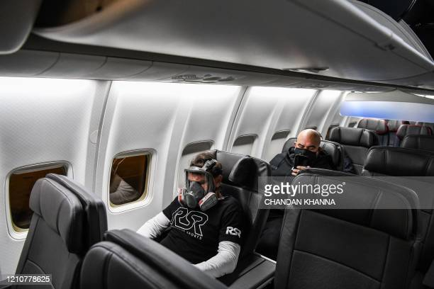 A man wears a gasmask as he travels in a flight from Miami to Atlanta in Miami on April 23 2020 The US Treasury is providing aid to the airlines as...