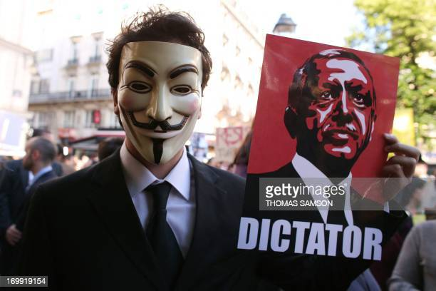A man wears a Guy Fawkes mask and holds a portrait of Turkish Prime Minister Recep Tayyip Erdogan with the word 'Dictator' as he takes part in a...