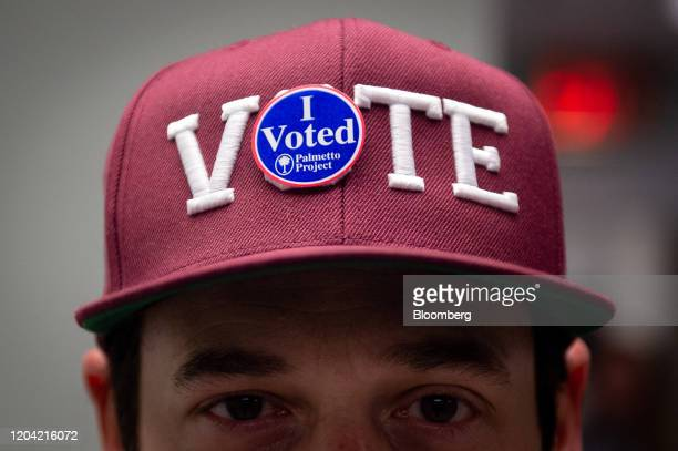 """Man wears a hat that reads """"VOTE"""" at a polling station in Charleston, South Carolina, U.S., on Saturday, Feb. 29, 2020. At stake in..."""