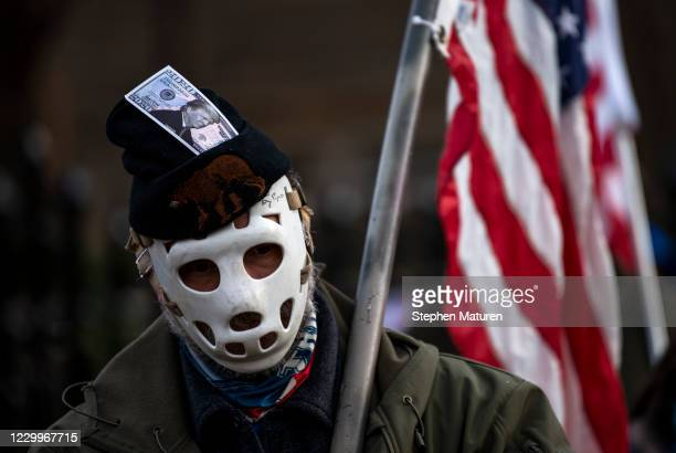 Man wears a hockey mask and a hat with a dollar bill imprinted with President Donald Trump looks on as protesters rally outside the Governor's...