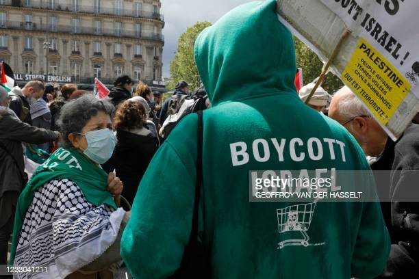 """Man wears a hoodie reading """"Boycott Israel"""" as protesters shout slogans and wave Palestinian flags during a demonstration in solidarity with the..."""