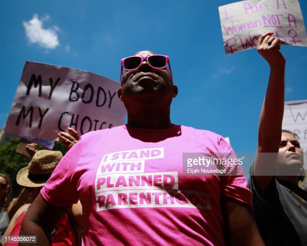A man wears a I stand with Planned Parenthood shirt at a protest against recently passed abortion ban bills at the Georgia State Capitol building on...