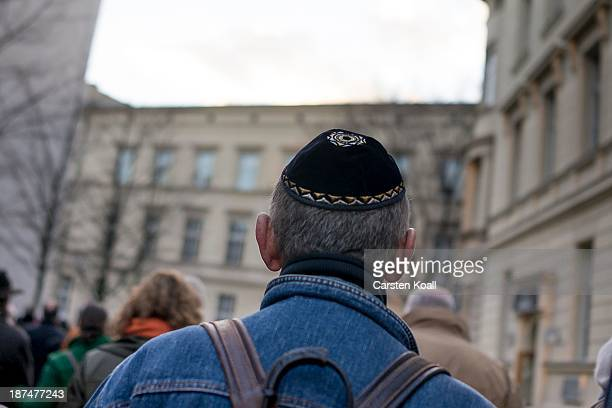 A man wears a kippa as he takes part in a silent march to commemorate the 75th anniversary of the Kristallnacht pogroms on November 9 2013 in Berlin...