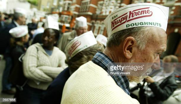 A man wears a Krispy Kreme hat whilst waiting to be allowed into the first Krispy Kreme shop in Harrods department store October 3 2003 in London