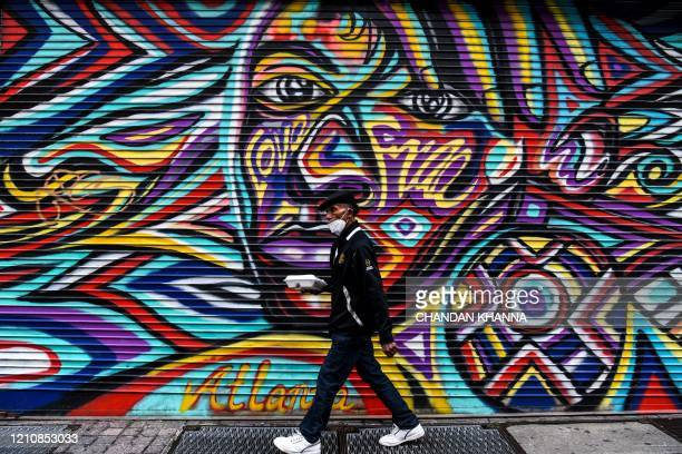 A man wears a mask amid fears over the spread of the novel coronavirus as he walks past a mural in downtown in Atlanta Georgia on April 23 2020 The...