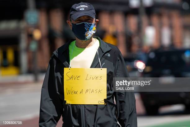 A man wears a mask and a sign urging others to wear masks as he walks in Baltimore's Inner Harbor in Maryland April 6 as the state continues a...