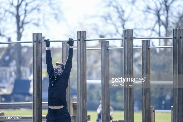 A man wears a mask and gloves while exercising on Clapham Common on March 25 2020 in London England British Prime Minister Boris Johnson announced...