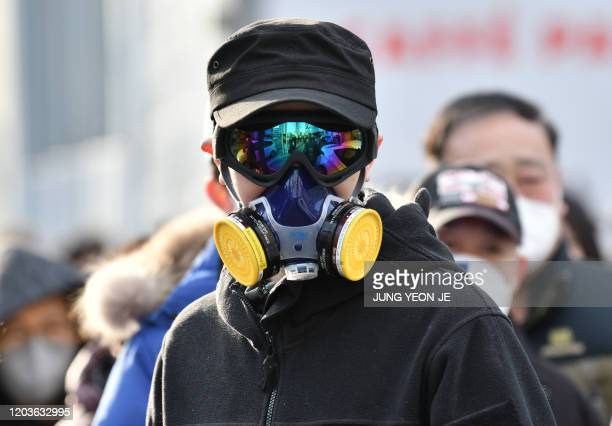 Man wears a mask and goggles as he waits in line to buy face masks from a post office near the Daegu branch of the Shincheonji Church of Jesus in...