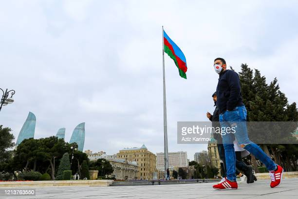 A man wears a mask and walking in Baku Boulevard in front of Flame Tower complex and the Azerbaijan flag during the eve of Nowruz festival on March...