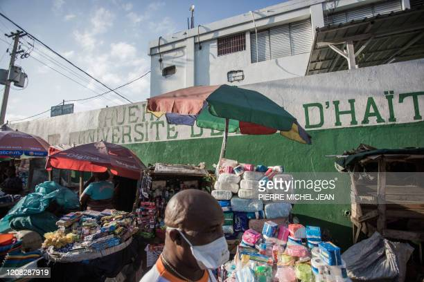 Man wears a mask as he walks past a stall selling good near the State Hospital in downtown Port-au-Prince on March 26, 2020. - On March 19, President...