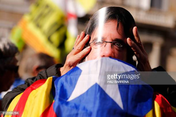 A man wears a mask depecting ousted separatist leader Carles Puigdemont during a demonstration on January 30 2018 in Barcelona The speaker of...