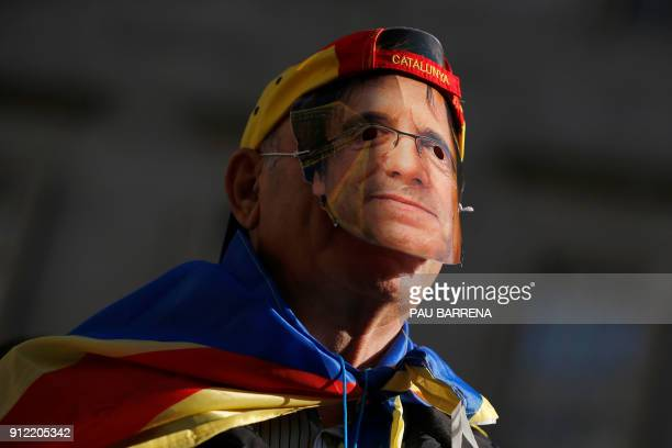TOPSHOT A man wears a mask depecting ousted separatist leader Carles Puigdemont during a demonstration on January 30 2018 in Barcelona The speaker of...