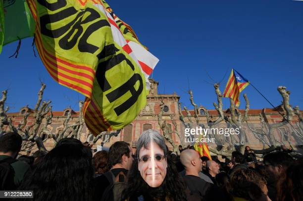 TOPSHOT A man wears a mask depecting ousted separatist leader Carles Puigdemont during a demonstration inside the enclosure of the Catalan Parliament...