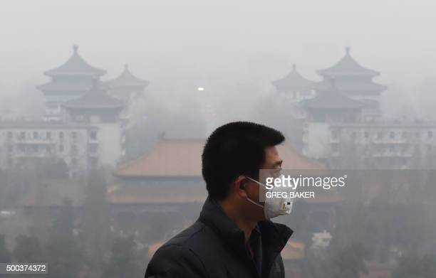 TOPSHOT A man wears a mask to protect himself from air pollution in Beijing on December 8 2015 Half of Beijing's private cars were ordered off the...