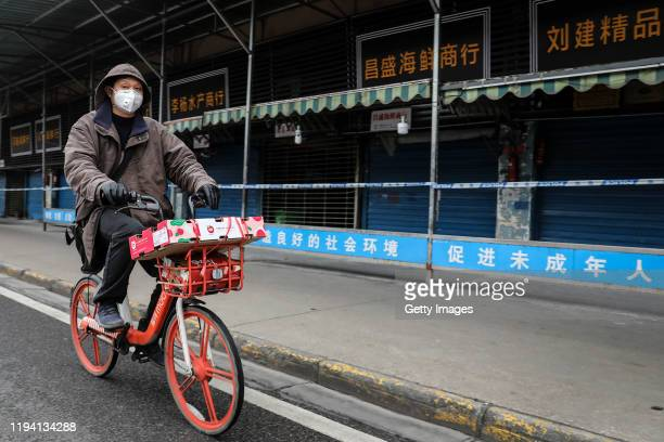 A man wears a mask while riding on mobike past the closed Huanan Seafood Wholesale Market which has been linked to cases of Coronavirus on January 17...