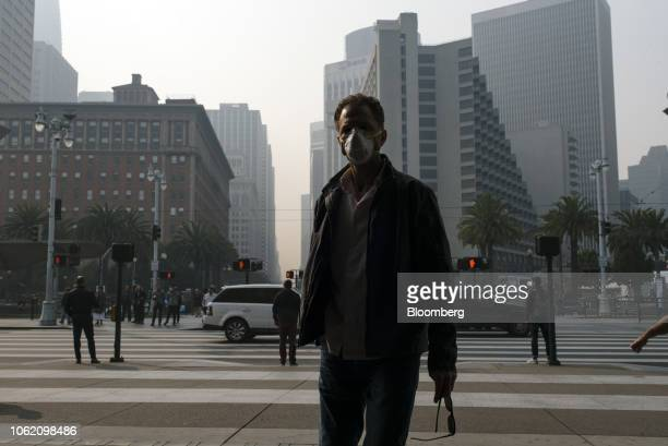 A man wears a mask while smoke from the Camp Fire fills the air in San Francisco California US on Thursday Nov 15 2018 The smoke from Californias...