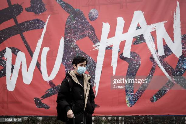"""Man wears a mask while walking in the street on January 22, 2020 in Wuhan, Hubei province, China. A new infectious coronavirus known as """"2019-nCoV""""..."""