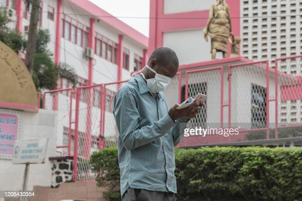 Man wears a mask while walking outside the entrance to the Yaounde General Hospital in Yaounde on March 6, 2020 as Cameroon has confirmed its first...