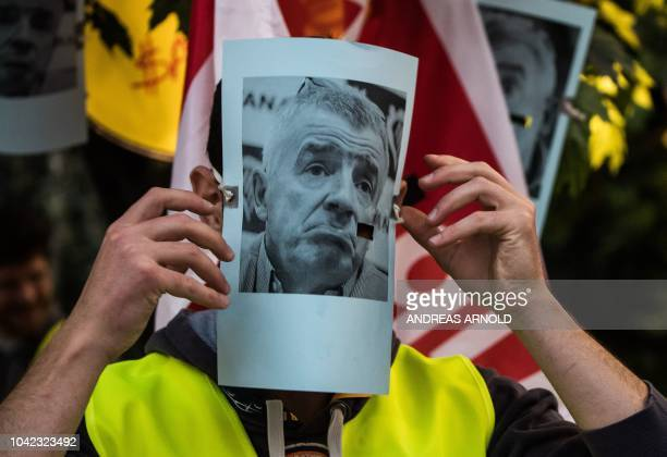 A man wears a mask with the portrait of Ryanair CEO Michael O'Leary as employees of Irish airline Ryanair stage a strike on September 28 2018 at the...