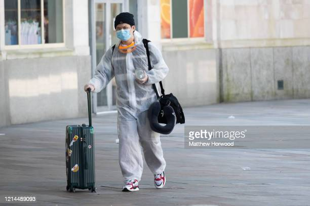 Man wears a protective coat, surgical mask and gloves at Cardiff Central train station on March 24, 2020 in Cardiff, United Kingdom. British Prime...