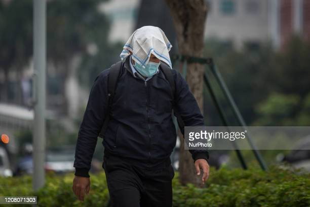 A man wears a protective face mask and cover his head with a cloth as he crosses the street in Jakarta Indonesia 23 March 2020 According to media...