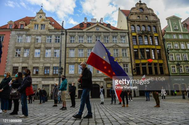 Man wears a protective face mask and holds Poland's and European Union flags as he takes part in an anti-government social distance protest during...