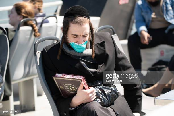 A man wears a protective face mask holding a religious law book in Hebrew on top of the NYC Ferry by Hornblower during the coronavirus pandemic on...