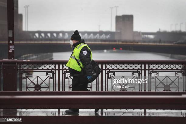 A man wears a protective face mask while walking across the Michigan Avenue bridge on March 19 2020 in Chicago Illinois Michigan Avenue normally a...