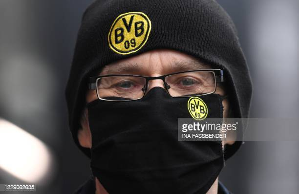 Man wears a protective face mask with the logo of German first division Bundesliga football club Borussia Dortmund as he walks in the pedestrian area...