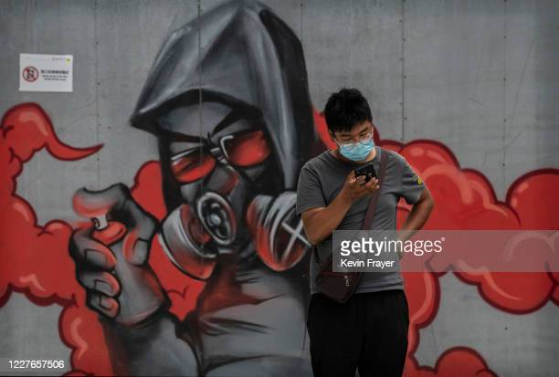 A man wears a protective mask as he looks at his phone next to graffiti art outside a mall on July 17 2020 in Beijing China Chinas economy returned...