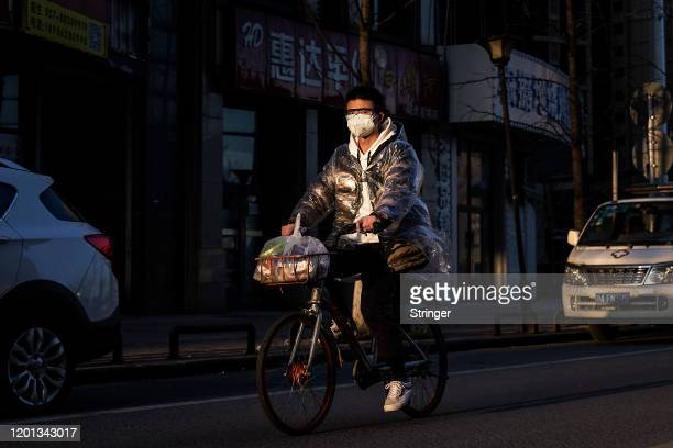 Man wears a protective mask as he ride bike in the street at Optical Valley on February 16, 2020 in Wuhan, Hubei province, China. Flights, trains and...