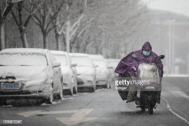 Man wears a protective mask as he rides a bike as snow falls on February 15, 2020 in Wuhan, Hubei, China. Flights, trains and public transport...