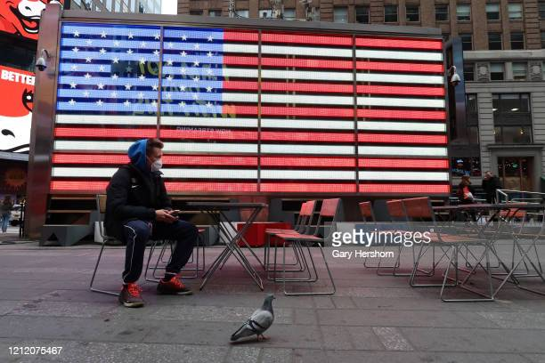 A man wears a protective mask as he sits in Times Square on March 12 2020 in New York City